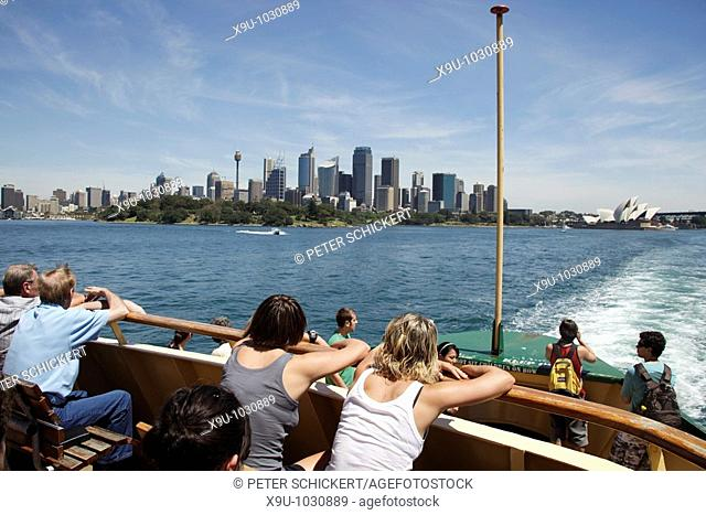 tourists on the Manly Ferry watching the Skyline and Opera in Sydney, New South Wales, Australia