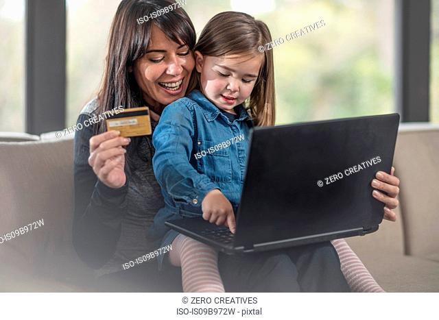 Girl and mother on sofa using laptop and credit card for online shopping