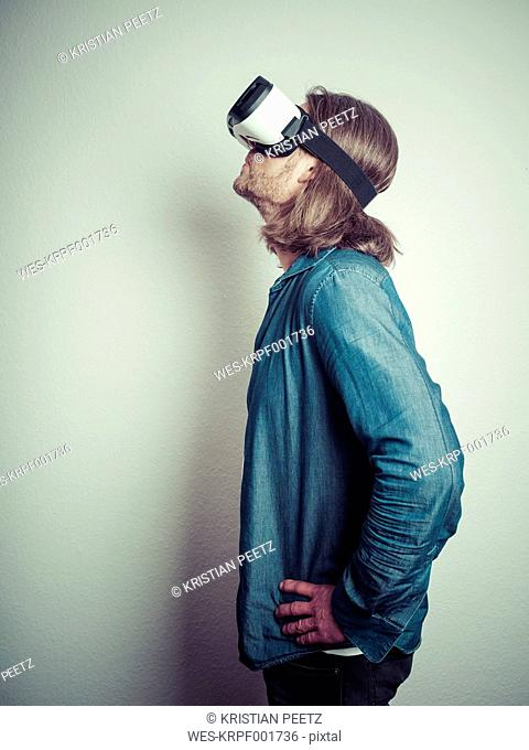 Man with hands on his hips wearing Virtual Reality Glasses looking up
