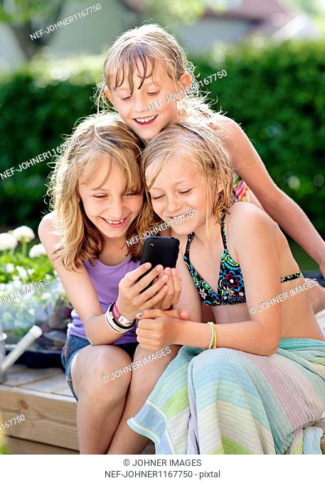 Three girls sitting in garden and texting on mobile phone