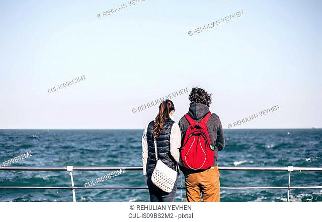Couple looking out from sea pier, rear view, Odessa, Odeska Oblast, Ukraine