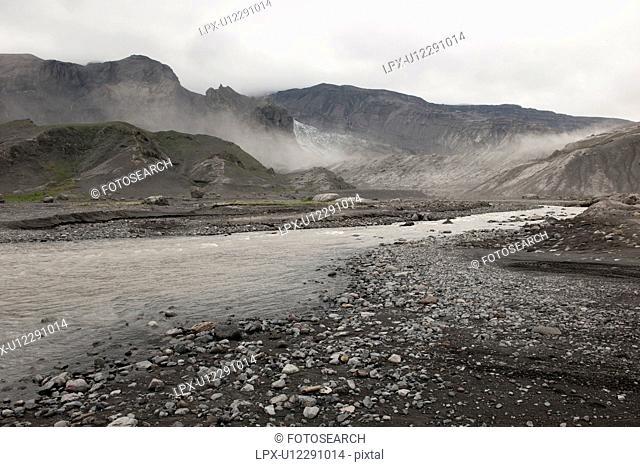 Rugged mountain landscape with river and mist rising