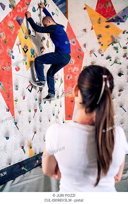 Climber watching friend on climbing wall