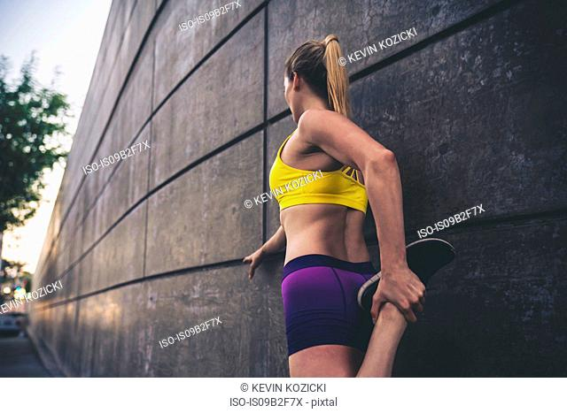Young woman stretching leg, leaning against wall