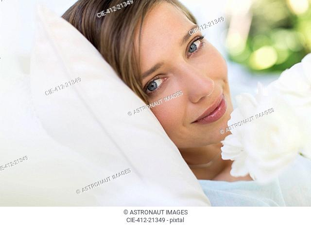 Close up of woman smelling flower on bed