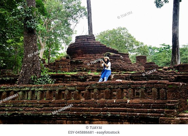 Travelers thai woman walking visit and travel take photo in ancient building and ruins of Kamphaeng Phet Historical Park is an archeological site and Aranyik...