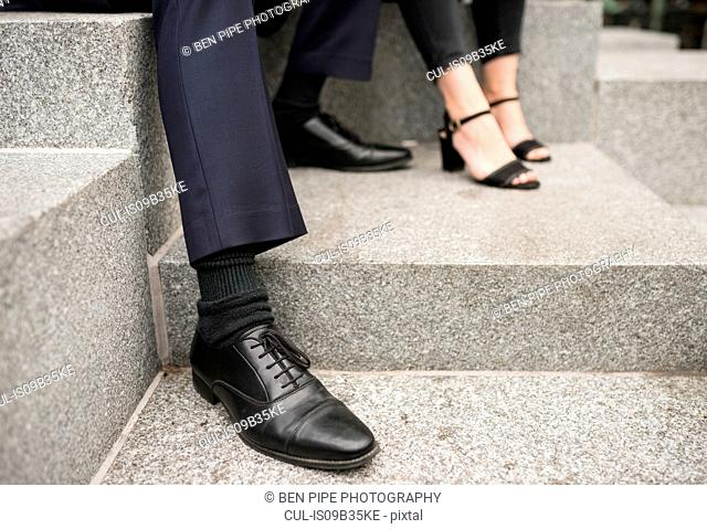 Cropped view of businesspersons' feet