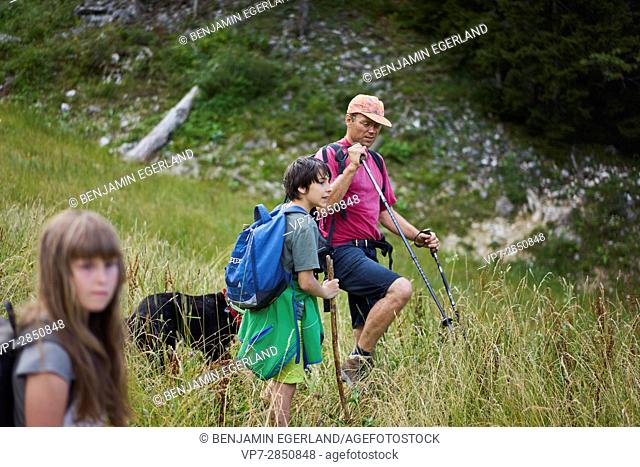 father with his children and dog during hiking adventure