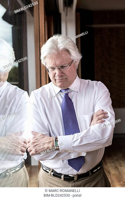 Pensive Caucasian businessman leaning on window