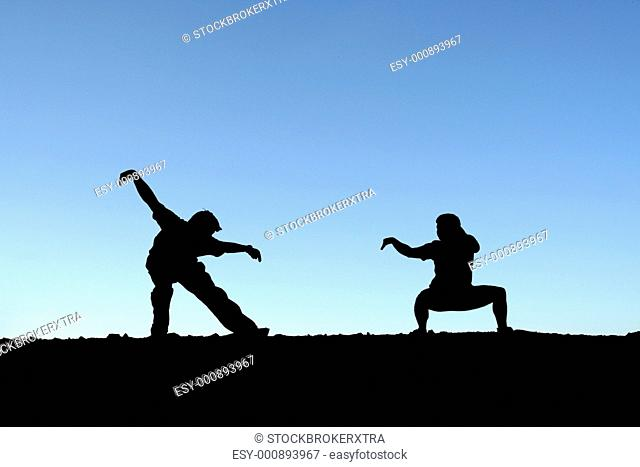 Two persons practicing martial arts on top of a mountain in silhouette