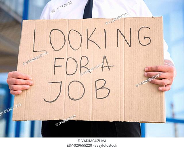Close-up of man in suit holding sign in hands. Unemployed man looking for job