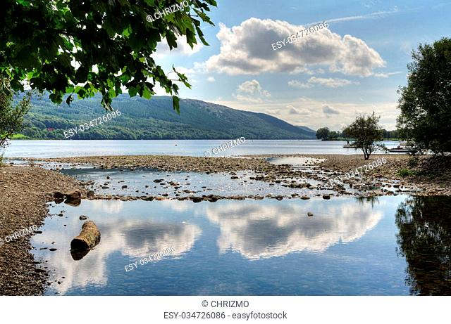 Cloud reflections in Coniston Water and an overhanging tree in the English Lake District, Cumbria