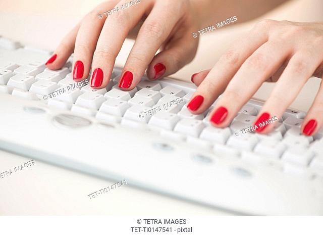 Close up of woman's fingers with red nail polish typing on computer keyboard