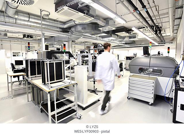 Man walking in a factory for manufacturing of circuit boards for the electronics industry