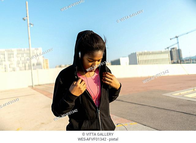 Young sportive woman listening music with headphones