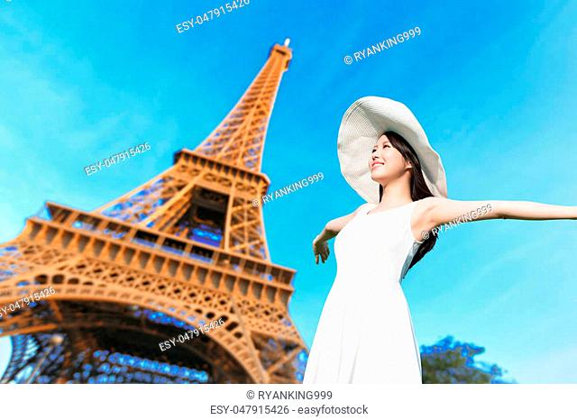 young woman wear dress and smile with eiffel tower