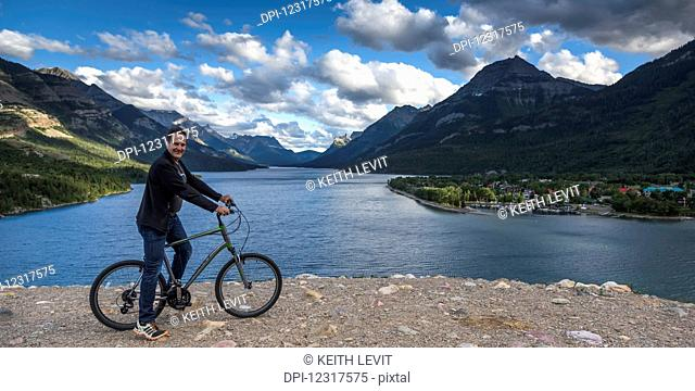 A man sits on a bicycle at the water's edge with the Rocky mountains and a lake in the background, Waterton Lakes National Park; Alberta, Canada
