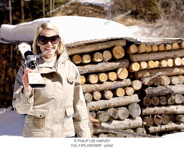 woman carrying skis by log pile