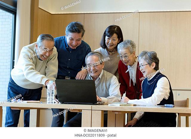 Senior people enjoying using PC