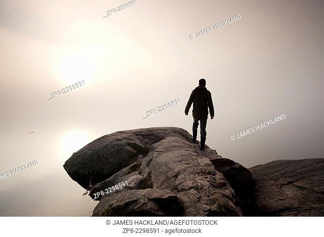 A man stands at the edge of a rocky outcrop looking into the fog as the sun rises. Algonquin Provincial Park, Ontario, Canada