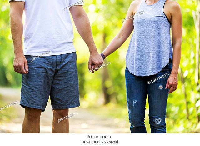 A married couple spending quality time together walking in a park; Edmonton, Alberta, Canada