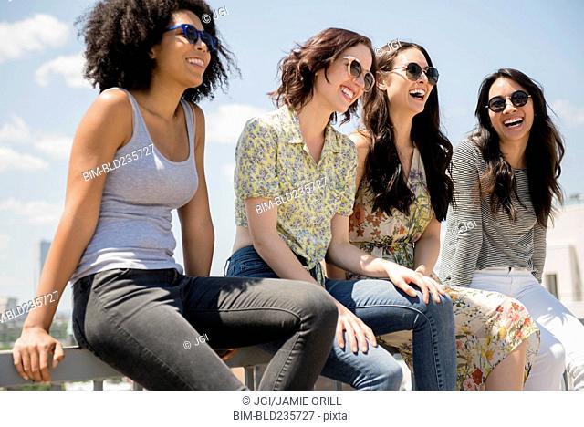Laughing women sitting on railing outdoors