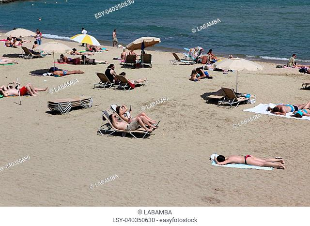 BARCELONA - JUNE 11: Crowded beach with tourists and locals in summer on June 11, 2013 in Barcelona, Spain. Barcelona is a famous destination for hundred of...