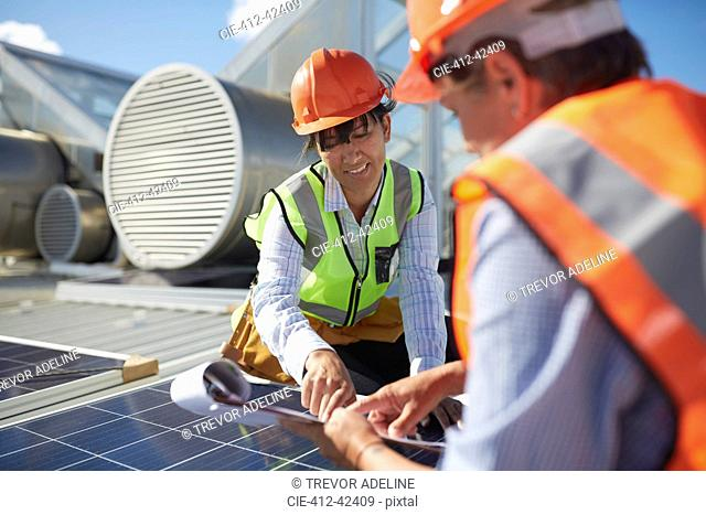Engineers with clipboard examining solar panel at sunny power plant