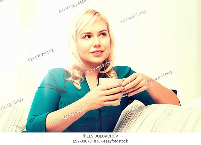 people and leisure concept - happy woman with cup of tea or coffee at home