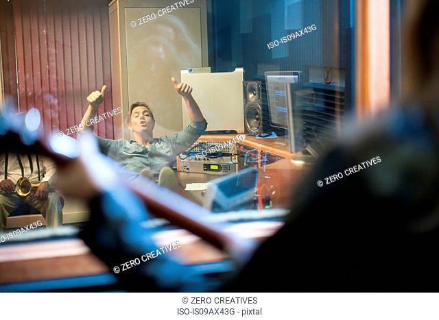 Music producer communicating to musician through studio window