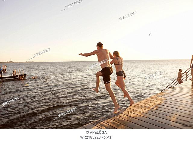 Rear view of couple jumping into sea from pier against clear sky