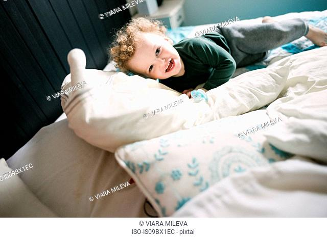 Boy smiling and playing on bed