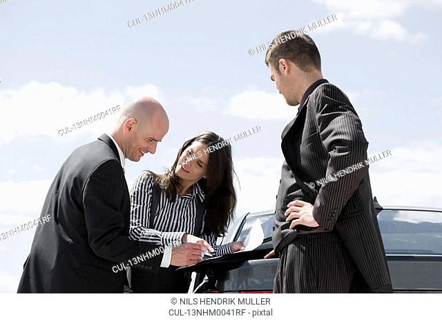 man signing contract on back of car