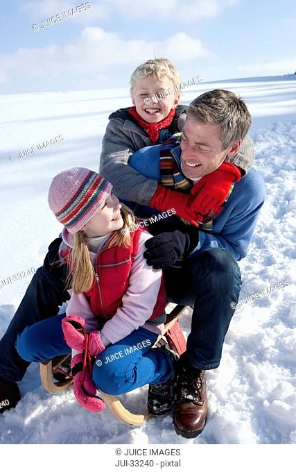 Smiling father with daughter and son on sled in snow