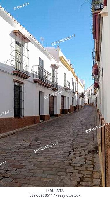 Typical street in the Spanish town of Carmona, houses are decorated with white brick facade, are bars and balcony on the windows
