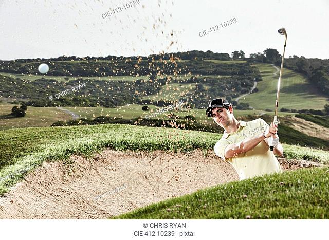 Man swinging from sand trap on golf course
