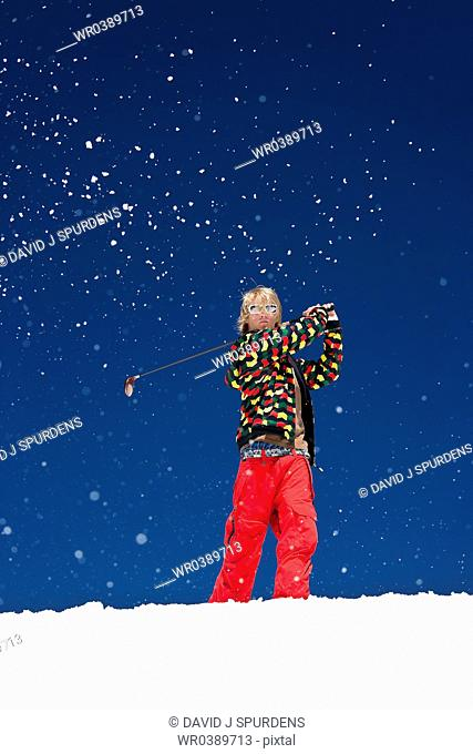 Golfer driving ball in snow