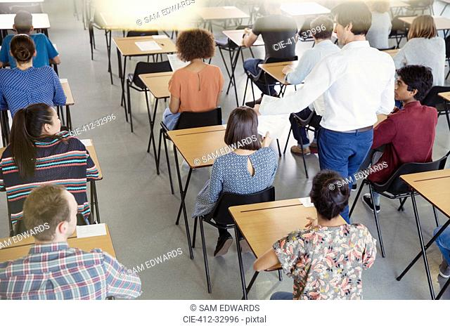 Professor collecting test from students in classroom