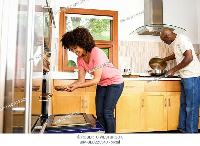 Black father and daughter cooking in kitchen