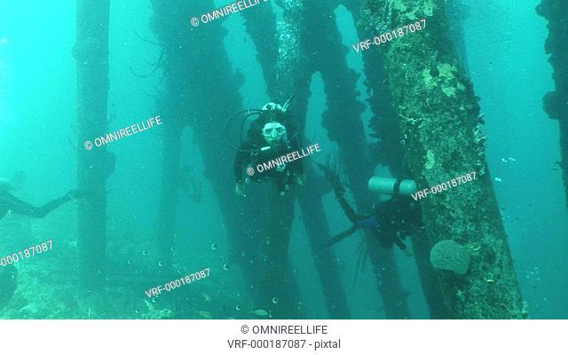 Female scuba diver swimming past camera