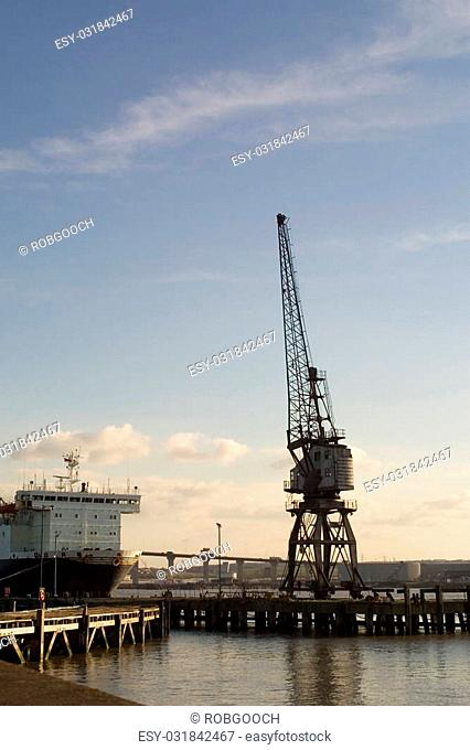 Crane and ship at dockside. Winter afternoon. Grays, Essex, UK