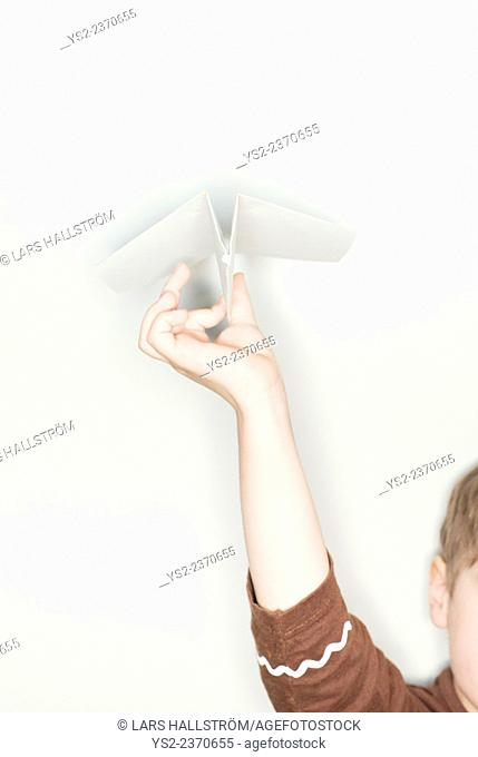Hand of child holding paper airplane