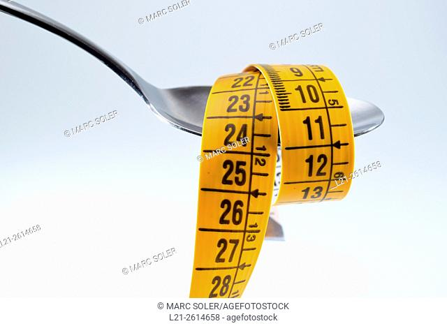 Spoon and measuring tape. Concept of food and weight loss