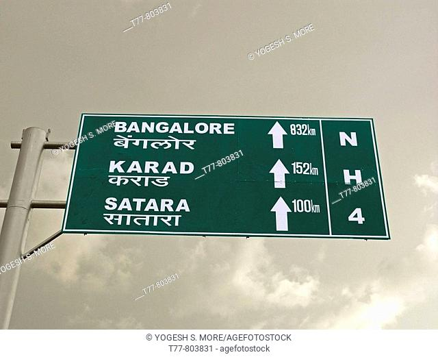 A signboard on a national highway four roadside is showing distances of Bangalore, Karad, Satara from Pune  Pune, Maharashtra, India