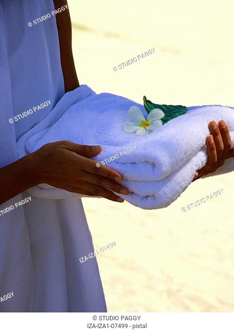 Mid section view of a woman holding a towel with Frangipani Plumeria flowers on it
