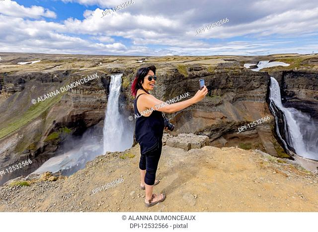 A young asian female hiker poses for a self-portrait on the edge of the Haifoss waterfall valley, a popular hiking destination in Iceland; Iceland