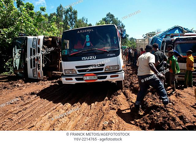 After the rain, the road is muddy. One truck is trying to pass while another overturned and another is blocked. Bedele in Oromia state, Ethiopia