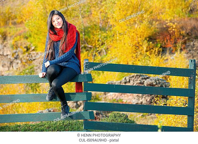 Mid adult woman wearing red wool scarf sitting on fence looking at camera smiling