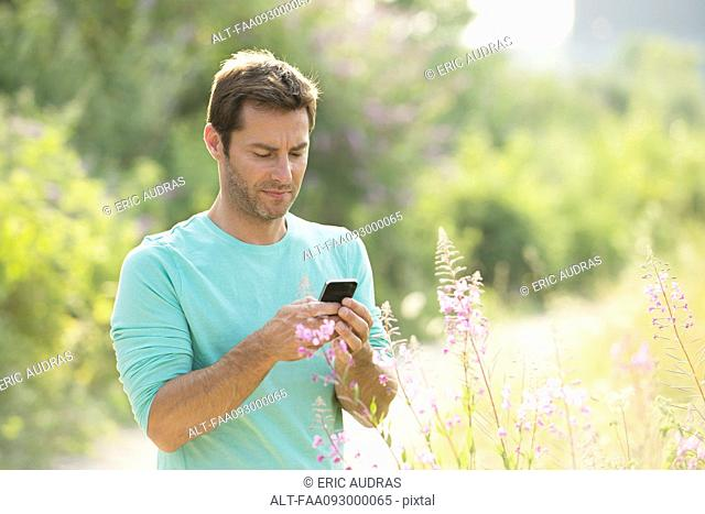 Mature man text messaging while enjoying the great outdoors