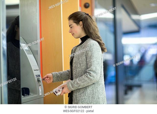 Young woman in a shopping mall using cash machine